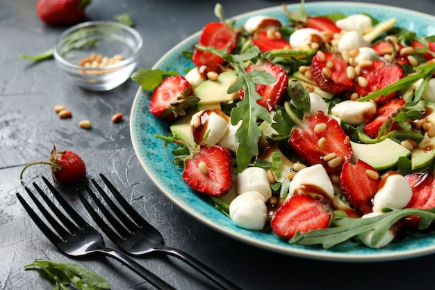 Healthy salad with strawberries, avocado, arugula and mozzarella, dressed with olive oil and balsamic dressing on dark Premium Photo