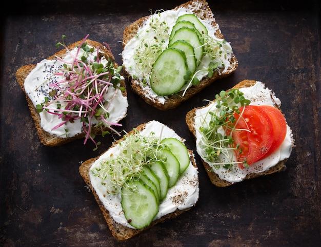 クリームチーズ、マイクログリーン、トマト、キュウリのヘルシーなサンドイッチ。健康的な食事、ダイエット食品、ビーガンフード Premium写真