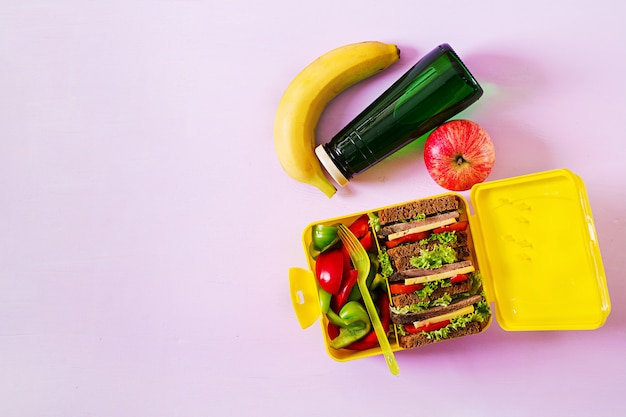 Healthy school lunch box with beef sandwich and fresh vegetables, bottle of water and fruits on pink table. top view. flat lay Free Photo