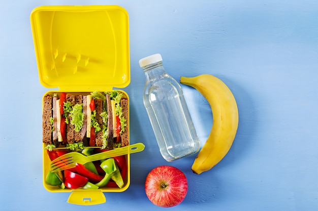 Healthy school lunch box with beef sandwich and fresh vegetables, bottle of water and fruits Free Photo