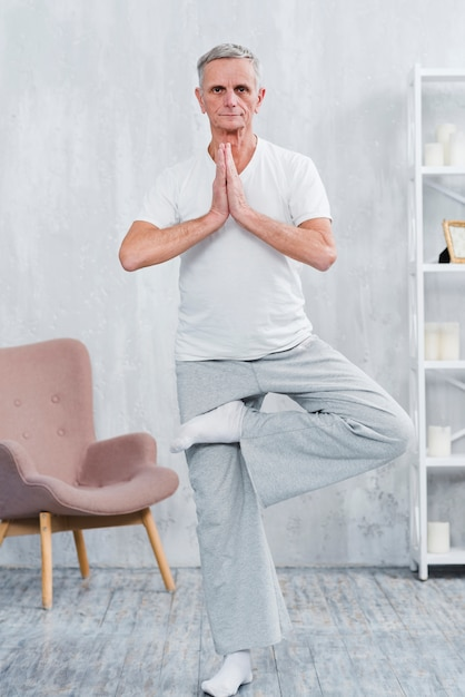 Healthy senior man practicing yoga looking at camera Free Photo