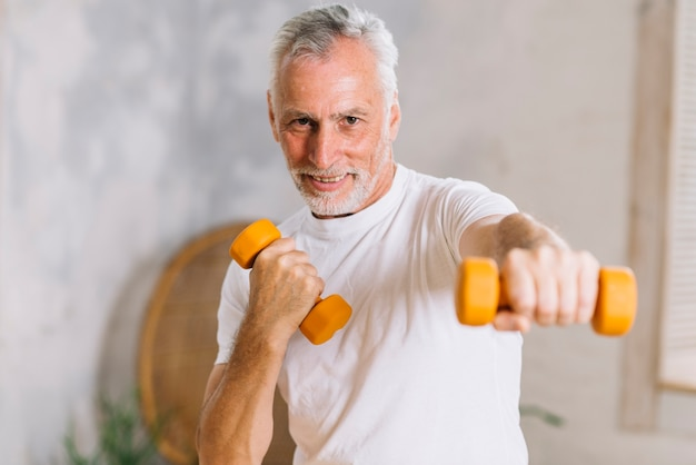 Healthy smiling senior man working out with dumbbells Free Photo