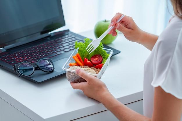 사무실 직장에서 건강 간식입니다. 비즈니스 여자 점심 식사 시간 동안 책상에서 점심 상자를 빼앗아에서 식사를 먹는 프리미엄 사진