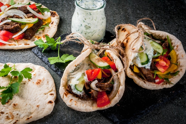Healthy snack, lunch. traditional greek wrapped sandwich gyros - tortillas, bread pita with a filling of vegetables, beef meat and sauce tzatziki Premium Photo