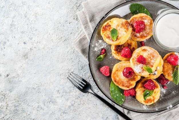 Healthy summer breakfast, cheese pancakes with raspberry Premium Photo