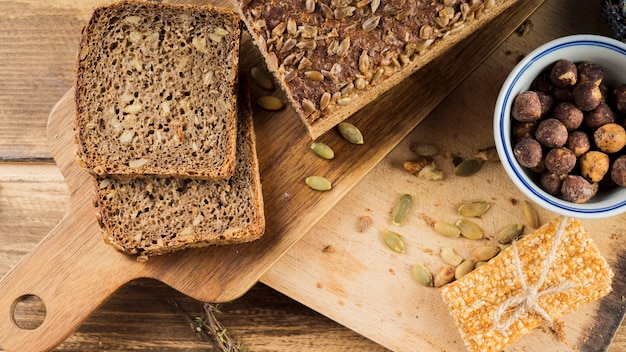 Healthy sunflower seed bread and hazelnut bowl with protein bar on chopping board Free Photo