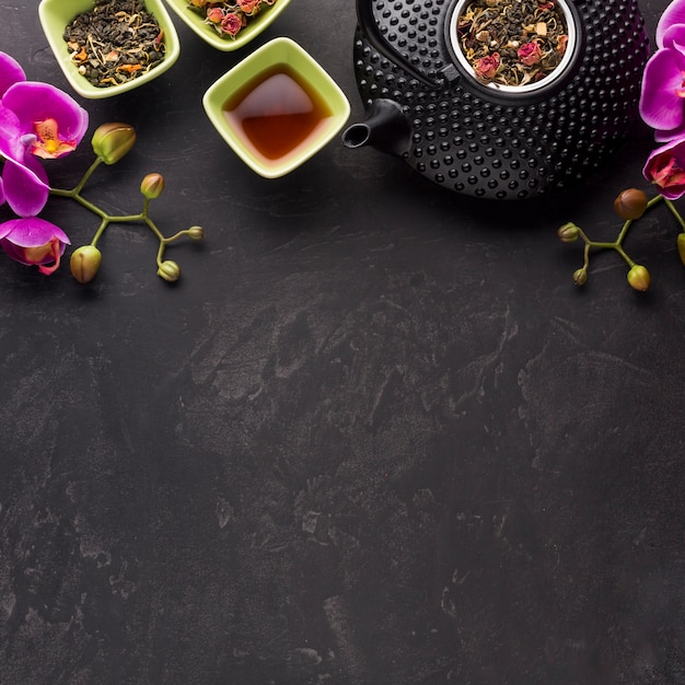 Healthy tea with dried ingredient and pink orchid flower on black background Free Photo