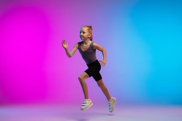 Salutare. ragazza adolescente, corridore professionista, pareggiatore in azione, movimento isolato su sfondo rosa-blu sfumato in luce al neon. concetto di sport, movimento, energia e stile di vita dinamico e sano. Foto Gratuite