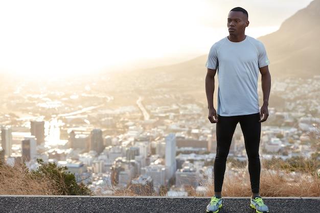 健康で思いやりのあるアスリートの男性で、体にフィットし、町の景色を背景に丘の上に立ち、カジュアルな服を着て、左側に広告コンテンツ用の空きスペースがあります。人、モチベーション、エネルギーの概念 無料写真