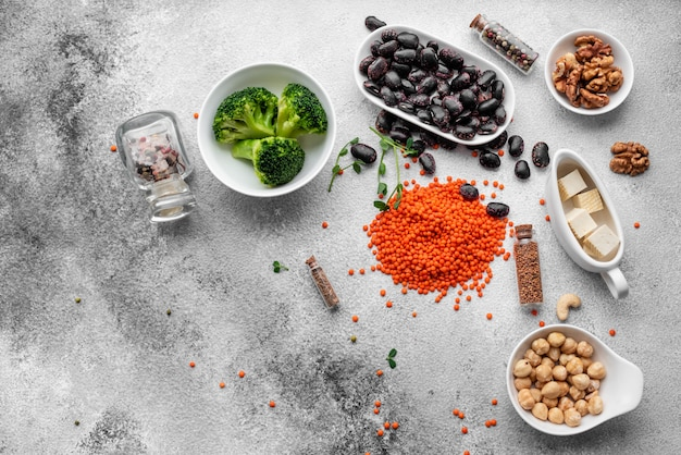 Healthy vegan food on a concrete background with copy space. nuts, beans, greens and seeds Premium Photo