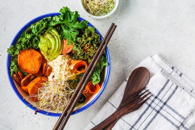 Healthy vegan lunch in white bowl. buddha bowl with avocados Premium Photo