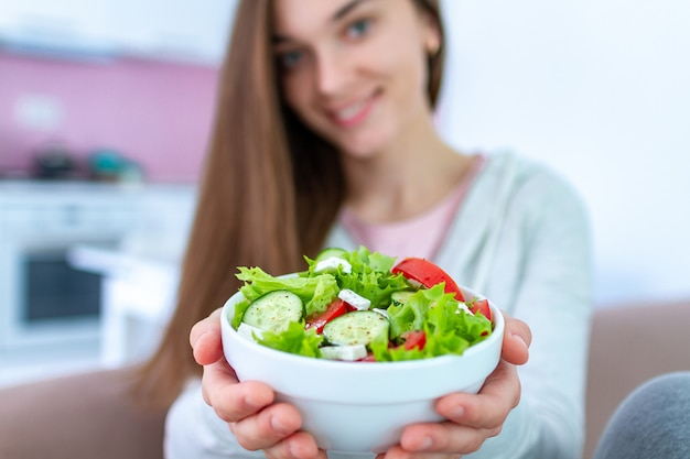 Healthy vegan woman holding a bowl of fresh vegetable salad. balanced organic diet and clean eating Premium Photo