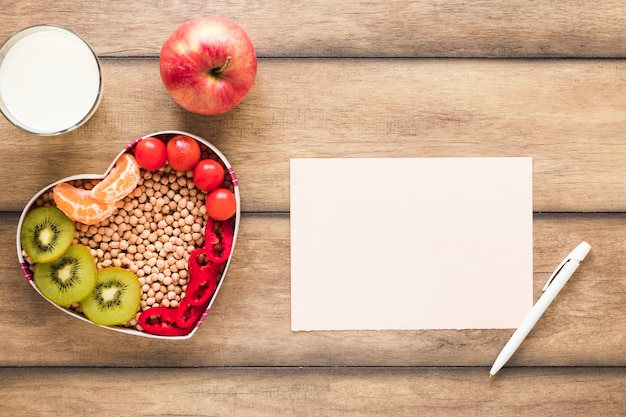 Healthy vegetables; fruits; milk with blank paper and pen on wooden table Free Photo