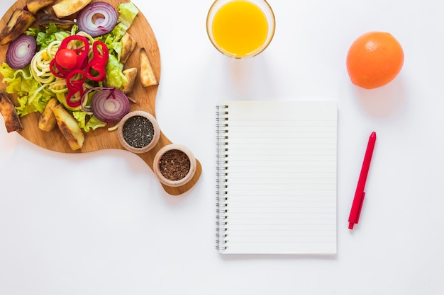 Healthy vegetables salad; juice; fruit; blank notepad and pen over white backdrop Free Photo