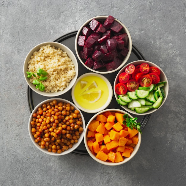 モロッコのサラダを調理するための健康的なベジタリアン食材。ひよこ豆、焼きカボチャとビート、キノアと野菜のトップビュー Premium写真