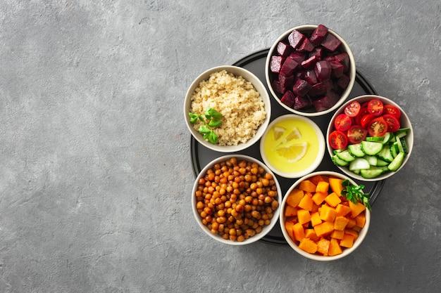 モロッコ風サラダを調理するためのヘルシーなベジタリアン食材。ひよこ豆、焼きカボチャとビート、キノアと野菜。 Premium写真