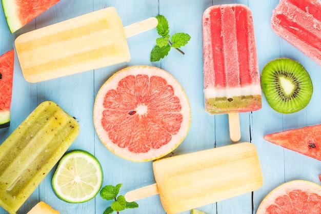 Здоровое фруктовое мороженое из цельных фруктов с ягодами киви, арбуз, дыня на деревянном винтажном столе Premium Фотографии