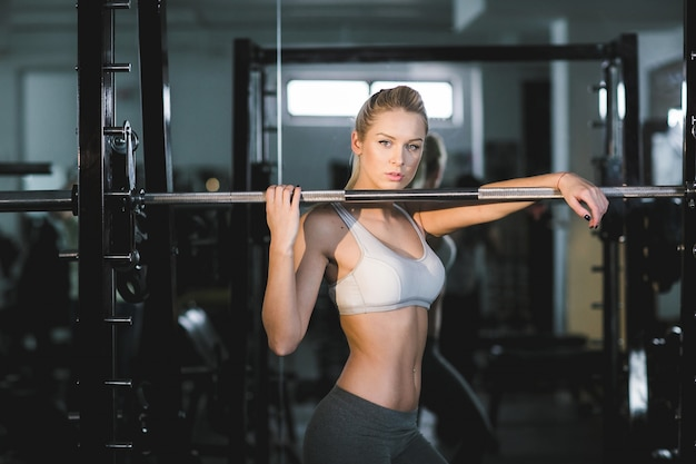 Healthy woman posing with a machine at the gym Free Photo