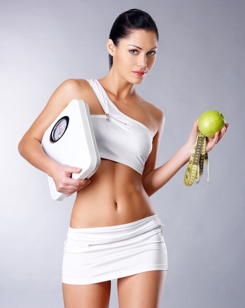 La donna in buona salute sta con le scale e la mela verde. concetto di mangiare sano. Foto Gratuite