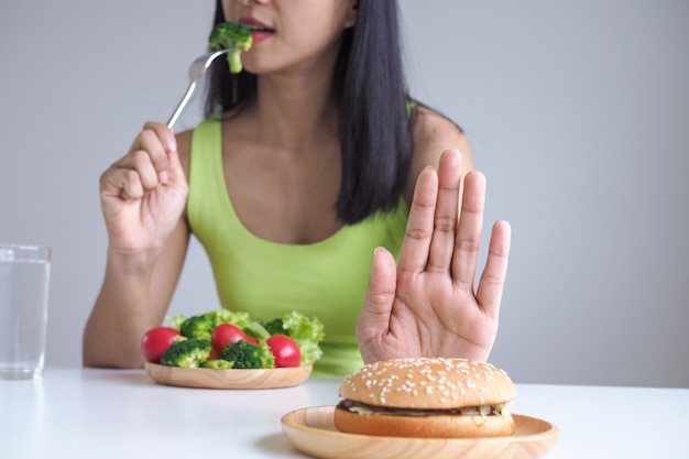 Healthy women choose to eat vegetable trays and refuse to eat hamburgers. Premium Photo
