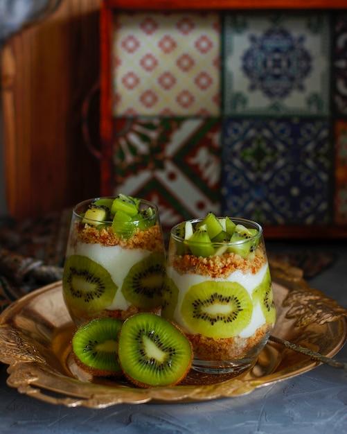 Healthy yogurt dessert with granola and fresh cut kiwi in tall glasses. Free Photo