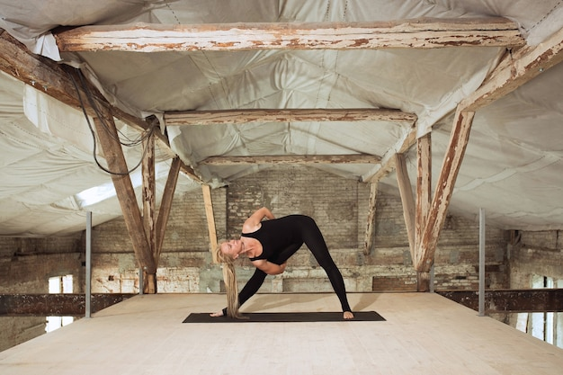 Healthy. a young athletic woman exercises yoga on an abandoned construction building. mental and physical health balance. concept of healthy lifestyle, sport, activity, weight loss, concentration. Free Photo