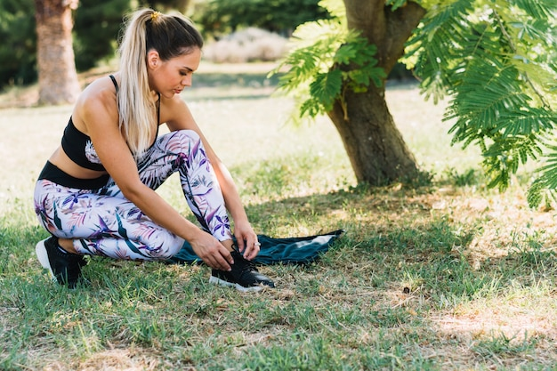 Healthy young woman tying her shoelace in the garden Free Photo