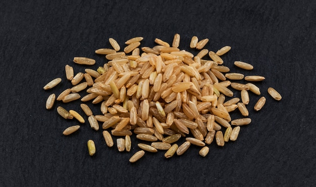 Heap of brown rice groats on black background Premium Photo