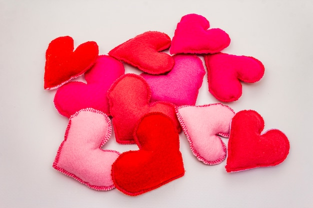 Heap of colored felt hearts isolated on white background. valentines day or wedding romantic concept Premium Photo