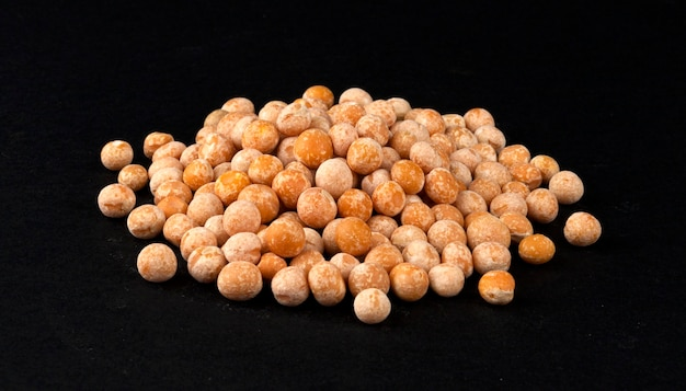 Heap of dried yellow pea isolated on black background, closeup Premium Photo
