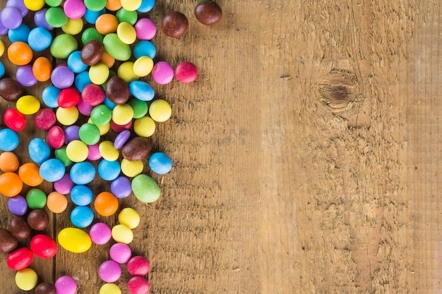 Heap of candy buttons on timber background Free Photo