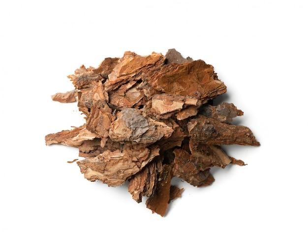 白で隔離される乾燥した松の木の樹皮片のヒープ。壊れた森の自然チップ Premium写真