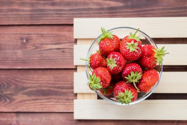 白い木製の背景上にボウルに、新鮮なイチゴのヒープ。有機ベリーと栄養の概念。それは抗酸化物質が豊富です。有機イチゴのボウル。新鮮な収穫の果物。新鮮な夏 Premium写真