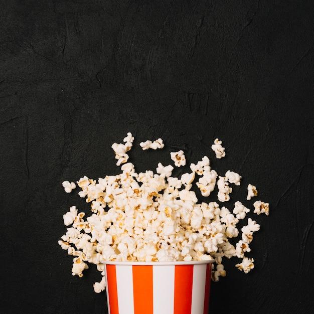 Куча попкорна, пролитая из полосатого ведра Premium Фотографии