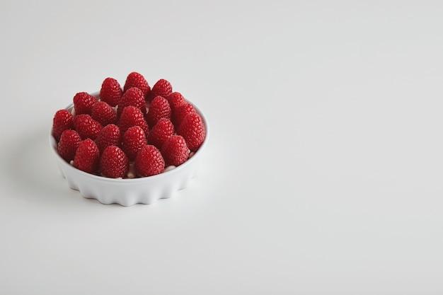 Куча спелой малины, точно помещенная в керамическую миску, изолированную на белом столе Бесплатные Фотографии
