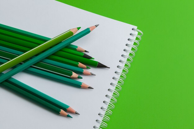 Heap of pencils on a bright green background Premium Photo