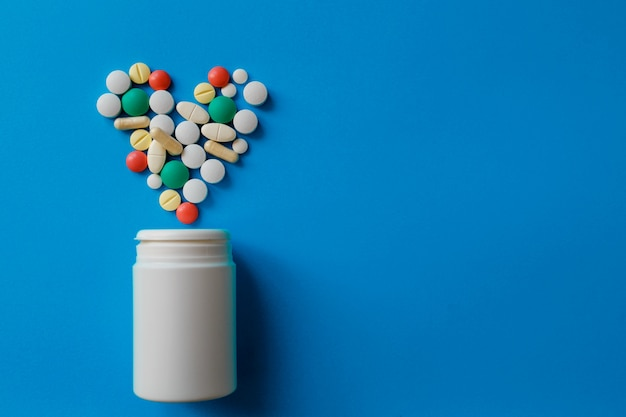 Heap of pills on blue  assorted pharmaceutical medicine pills, tablets and capsules and bottle on blue Premium Photo