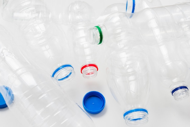 Heap of plastic bottles and caps on grey background Free Photo