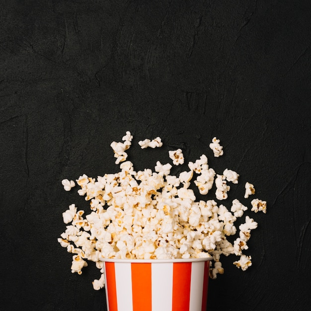 Heap of popcorn spilled from striped bucket Free Photo