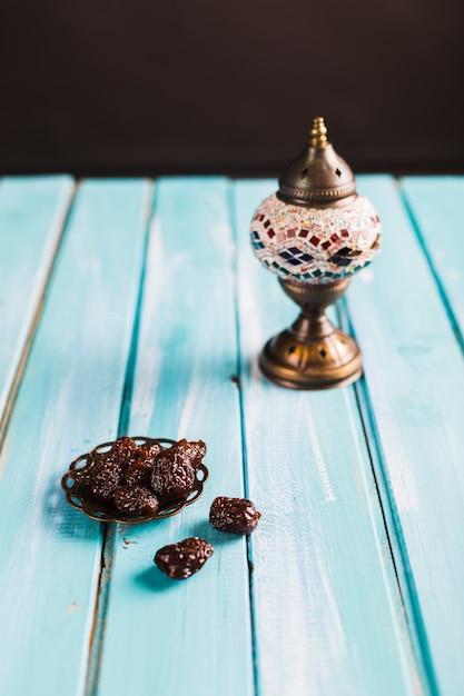 Heap of prunes on saucer near wonderful tableware on table Free Photo