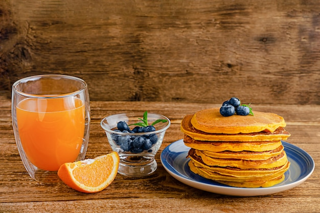Heap of pumpkin pancakes with blueberries and orange juice on rustic wooden table. copy space. Premium Photo