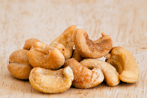 Heap of a roasted cashew nuts on an old wooden table. Free Photo