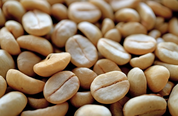 Heap of unroasted coffee beans with selective focus and blurred background Premium Photo