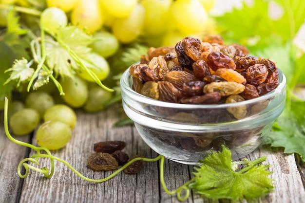 Heap of white raisins on wooden background and grape Premium Photo