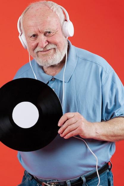 年配の男性がheaphonesで音楽を聴く 無料写真
