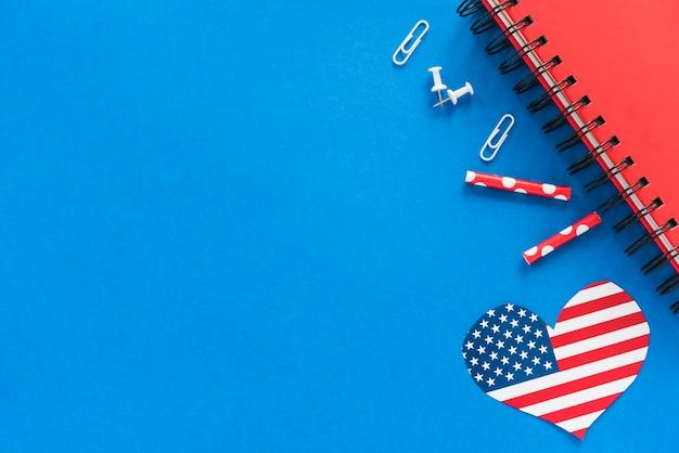 Cuore nel colore della bandiera americana e cancelleria sulla superficie blu Foto Gratuite