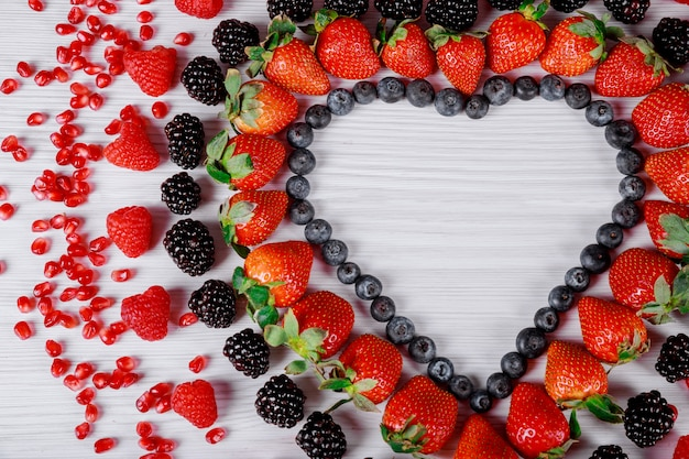 Heart of berries on wooden background Premium Photo