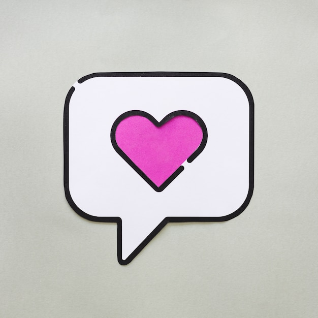 Heart in bubble speech icon on grey table Free Photo