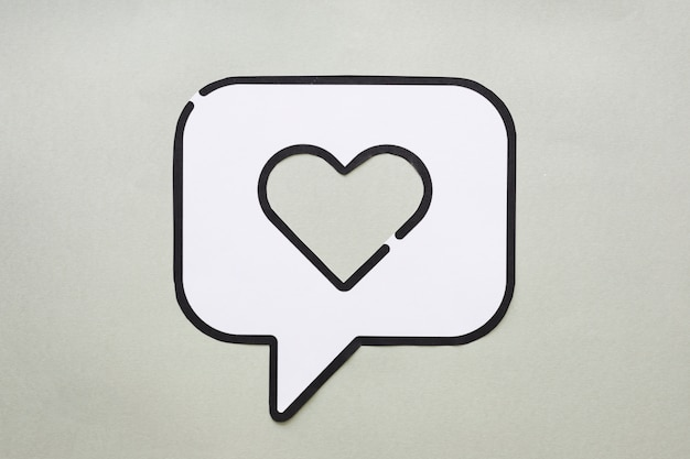 Heart in bubble speech icon on table Free Photo