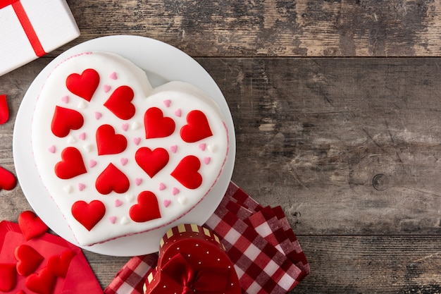 Heart cake for st. valentine's day decorated with sugar hearts on wooden table Premium Photo
